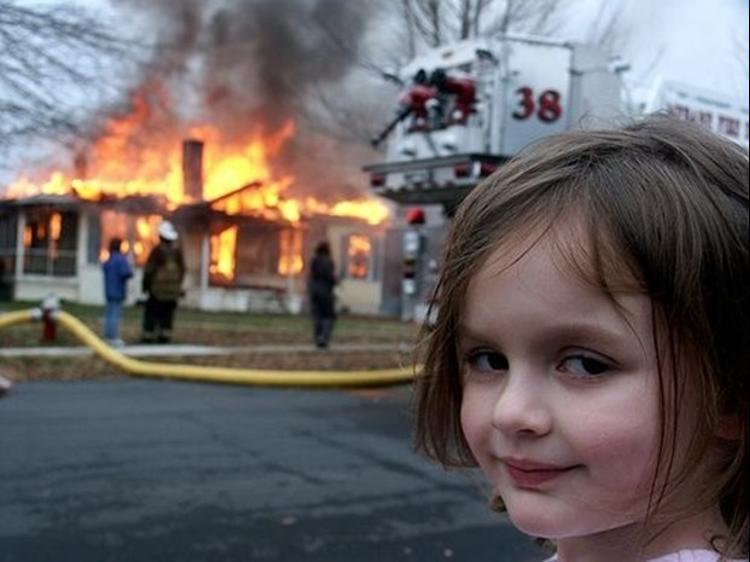 Foto mostra casa pegando fogo em segundo plano, em frente uma criança olha para a câmera e sorri.